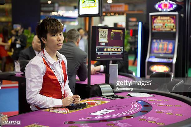 A croupier stands at a poker table at the Bally Technologies Inc booth at the Global Gaming Expo inside the Venetian Macao resort and casino operated...