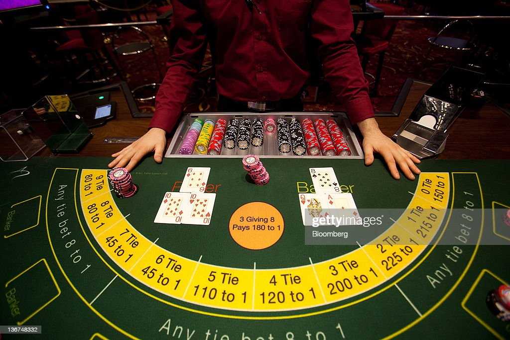 A croupier stands behind cards and gaming chips on a card table at Aspers Casino at Westfield Stratford City Mall in London, U.K. on Wednesday, Jan. 11, 2012. Westfield Group agreed to sell its 75 percent interest in the Broadmarsh shopping center to Capital Shopping Centres for 55 million pounds. Photographer: Simon Dawson/Bloomberg via Getty Images