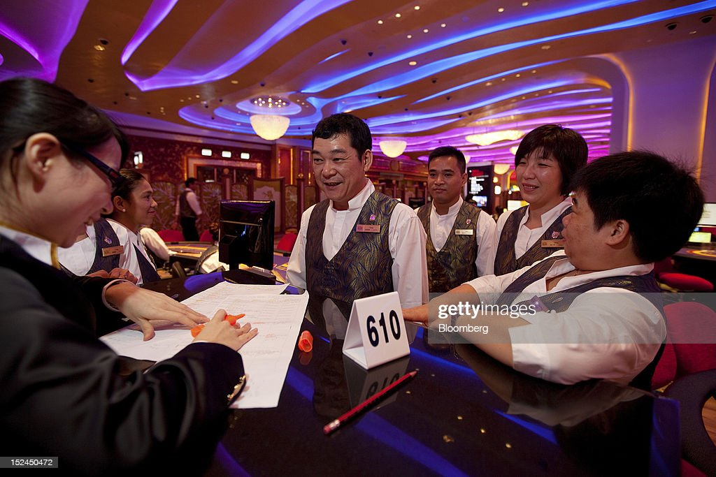 Croupiers receive their table assignments in the Sands Cotai Central casino resort, owned by Sands China Ltd., a unit of Las Vegas Sands Corp., in Macau, China, on Thursday, Sept. 20, 2012. Billionaire Sheldon Adelson's casino operator Las Vegas Sands Corp. plans to invest at least $2.5 billion to build its fifth resort in Macau, where gambling revenue is forecast to rise to $100 billion by 2020. Photographer: Daniel J. Groshong/Bloomberg via Getty Images
