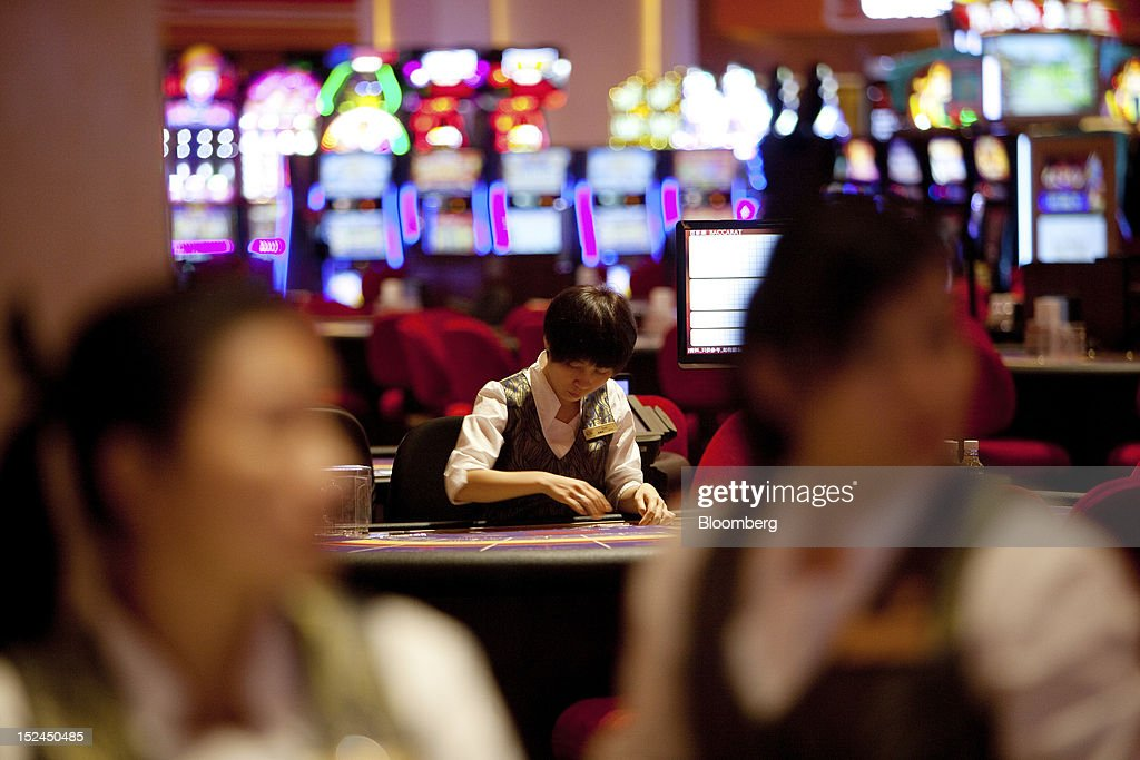 Croupiers stand at card tables in the Sands Cotai Central casino resort, owned by Sands China Ltd., a unit of Las Vegas Sands Corp., in Macau, China, on Thursday, Sept. 20, 2012. Billionaire Sheldon Adelson's casino operator Las Vegas Sands Corp. plans to invest at least $2.5 billion to build its fifth resort in Macau, where gambling revenue is forecast to rise to $100 billion by 2020. Photographer: Daniel J. Groshong/Bloomberg via Getty Images