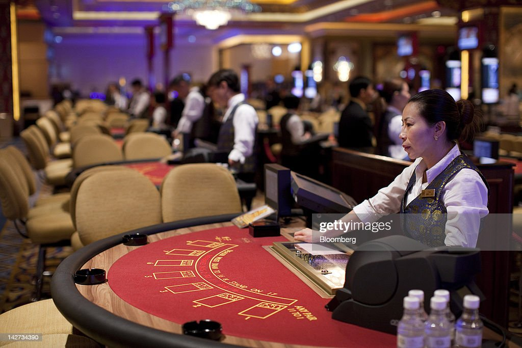 Croupiers stand at their tables in the Sands Cotai Central casino resort in Macau, China, on Wednesday, April 11, 2012. Las Vegas Sands Corp. Chairman Sheldon Adelson plans to spend $35 billion on building Spanish gambling resorts over nine years and will add a new Macau location to expand globally. Photographer: Jerome Favre/Bloomberg via Getty Images