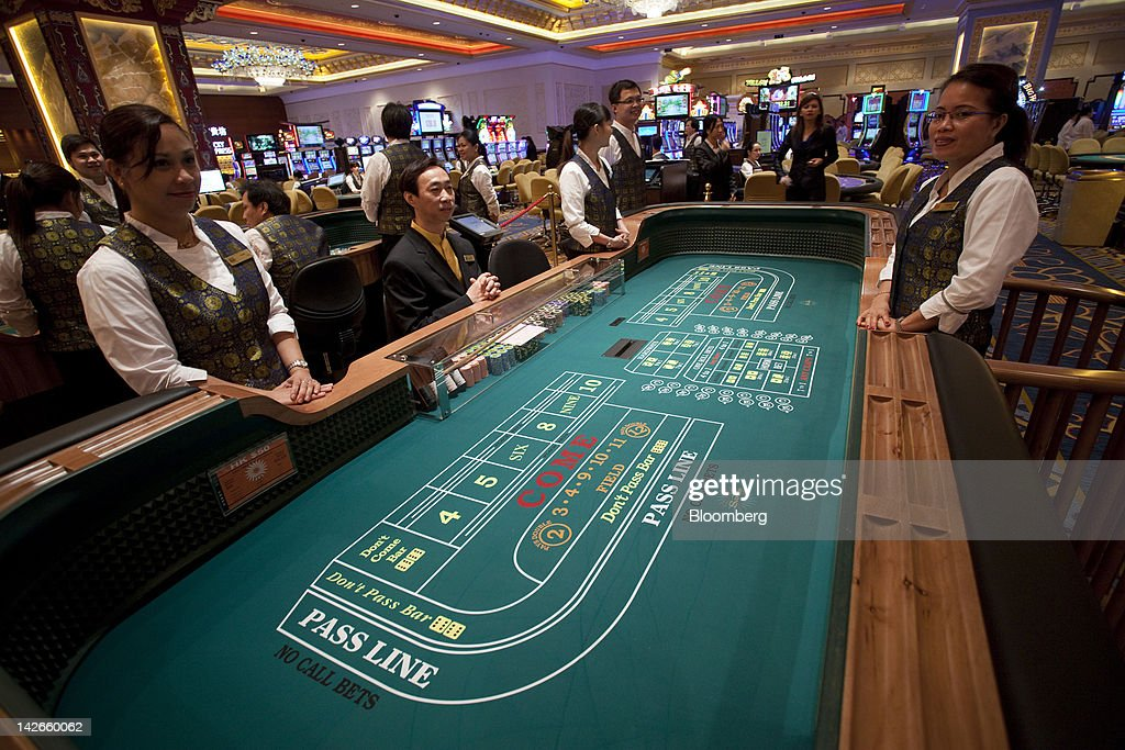 Croupiers stand by a craps table in the Sands Cotai Central casino resort on its opening day in Macau, China, on Wednesday, April 11, 2012. Las Vegas Sands Corp. Chairman Sheldon Adelson plans to spend $35 billion on building Spanish gambling resorts over nine years and will add a new Macau location to expand globally. Photographer: Jerome Favre/Bloomberg via Getty Images