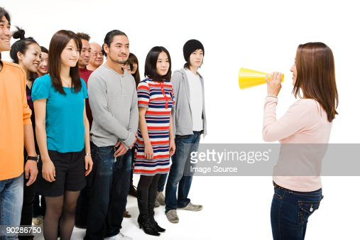 Crowd and woman with loudspeaker : Stock Photo