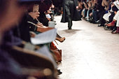 Unrecognizable crowd sitting in row on fashion show