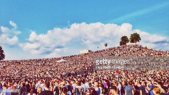 Crowd At Festival On Hill Against Cloudy Sky