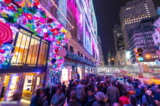Crowd at front of Saks Fifth Avenue window displays, which are illuminated by 2016 Saks Fifth Avenue Holiday Light Show at night in Midtown Manhattan. Exterior of Saks Fifth Avenue and window displays are decorated for Christmas decoration.