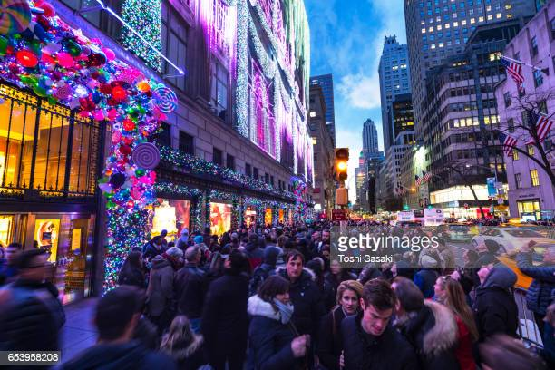 Crowd at front of Saks Fifth Avenue window displays, which are illuminated by 2016 Saks Fifth Avenue Holiday Light Show at dusk in Midtown Manhattan. Exterior of Saks Fifth Avenue and window displays are decorated for Christmas decoration.