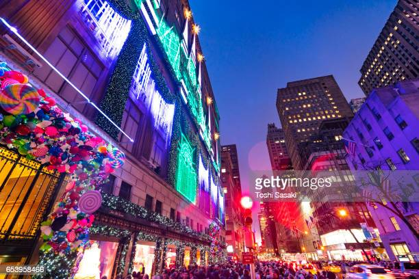 Crowd at front of Saks Fifth Avenue window displays, which are illuminated by 2016 Saks Fifth Avenue Holiday Light Show at snow night in Midtown Manhattan. Exterior of Saks Fifth Avenue and window displays are decorated for Christmas decoration.