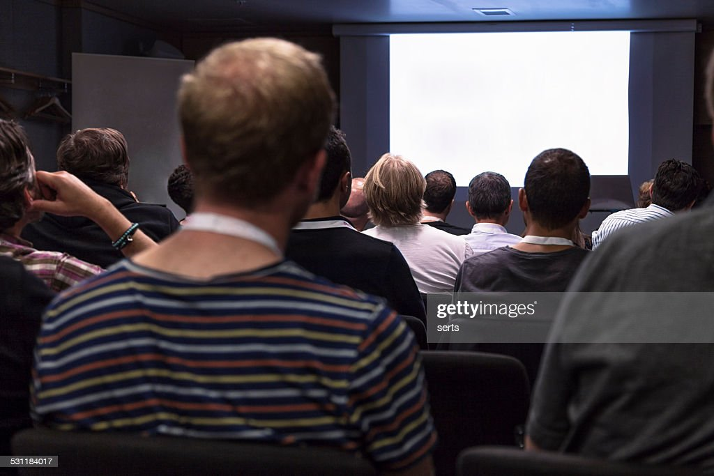 Crowd audience looking at blank screen : Stock Photo