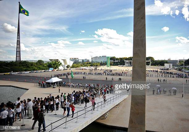 A crowd awaits in line outside Brazilian architect Oscar Niemeyer's funeral at Planalto Palace in Brasilia on December 6 2012 Niemeyer the Brazilian...