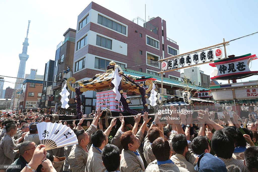 A crowd carries one of the three Asakusa Shrineowned portable shrine or mikoshi as they parade through the streets during the Sanja Festival on May...
