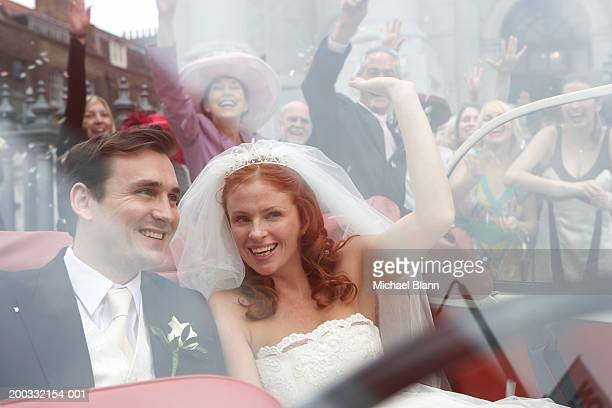 Crowd cheering bride and groom parting in open top car, close-up