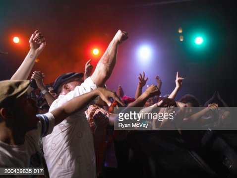 Crowd cheering in front of stage in nightclub, arms raised, side view : Stock Photo
