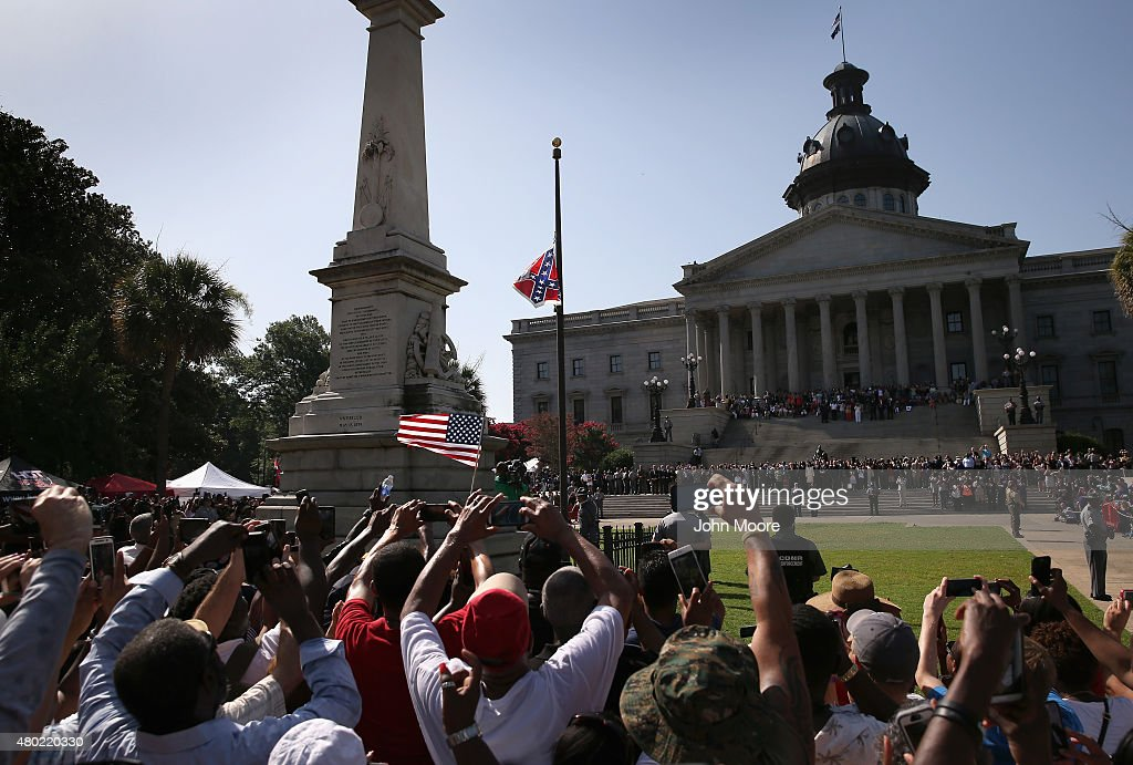 A crowd cheers as a South Carolina state police honor guard lowers the Confederate flag from the Statehouse grounds on July 10 2015 in Columbia South...