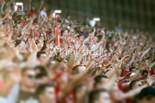 Crowd clapping on the podium of the stadium : Stock Photo