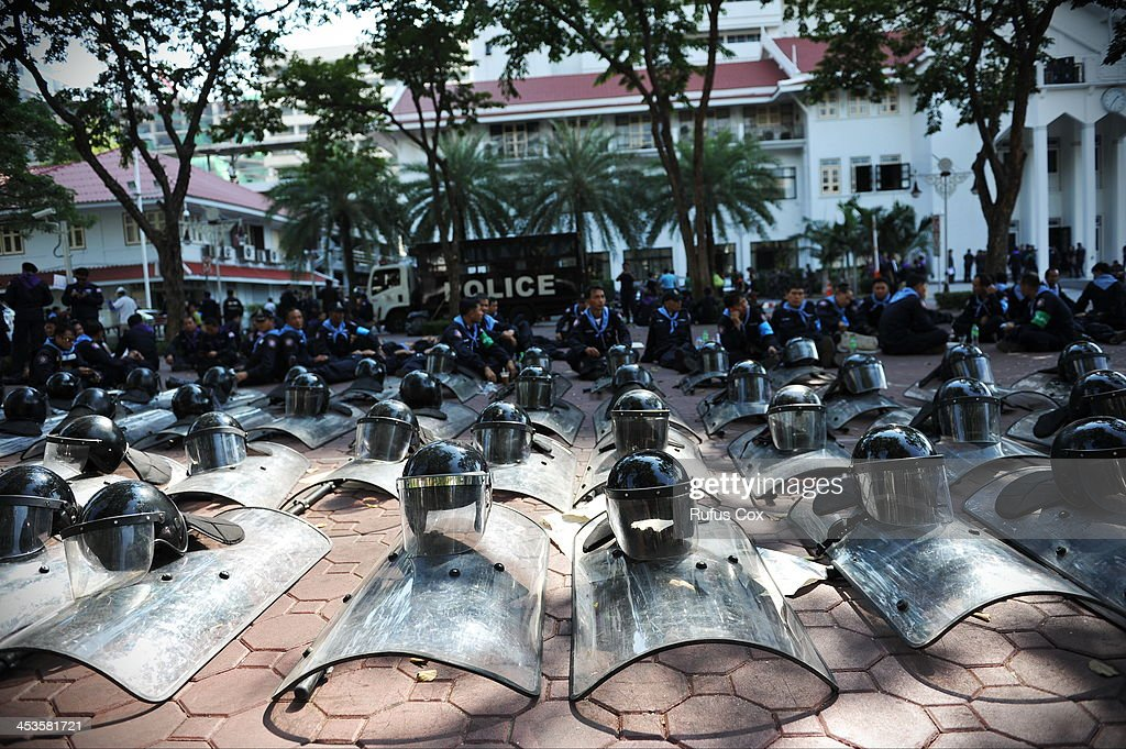 Crowd control police take a rest at the Royal Thai Police HQ after anti-government protesters hold a brief symbolic occupation of the compound on December 4, 2013 in Bangkok, Thailand. Protesters were allowed to briefly enter the compound amid easing tensions in the run up to the Thai king's birthday on Thursday. In marking the king's birthday anti-government protesters have declared a temporary truce in their campaign to topple the government.