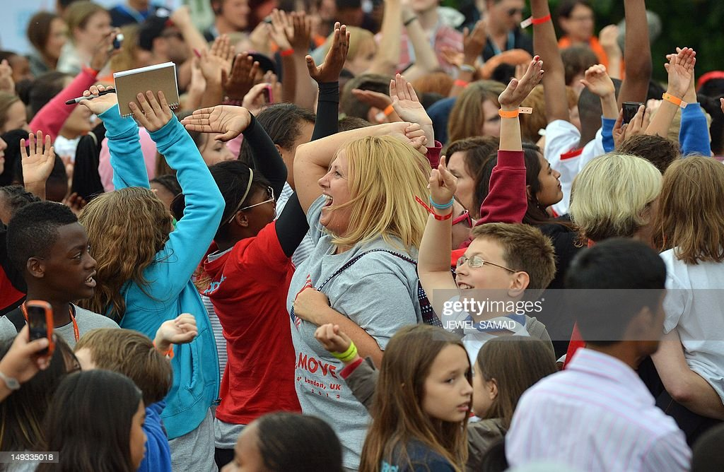 Crowd dance as British-Irish boy band The Wanted perform on stage during US First Lady's 'Let's Move-London' event at the Winfield House in London on July 27, 2012, hours before the start of the London 2012 Olympic Games. AFP PHOTO/Jewel Samad