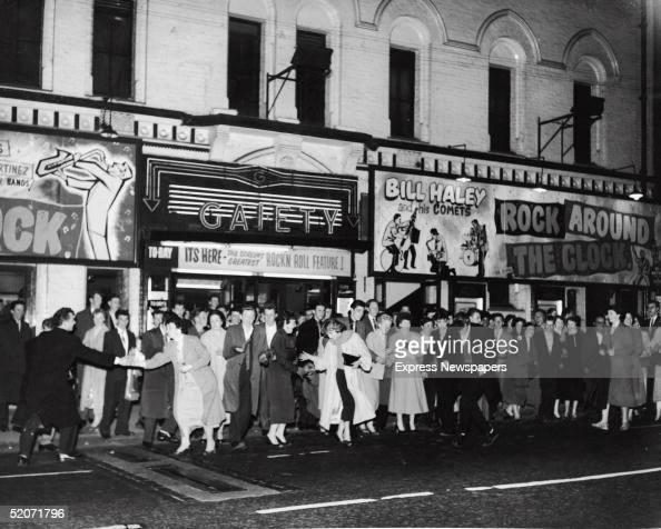 A crowd dances on the sidewalk outside the Gaiety Cinema which is showing 'Rock Around the Clock' starring American rock and roll band Bill Haley and...