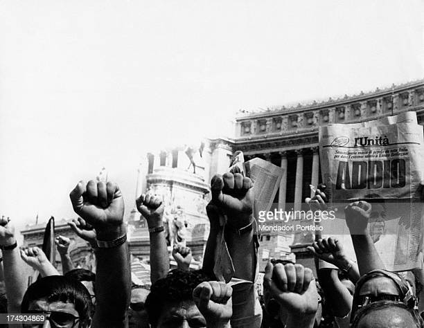 Crowd doing the clenched fist salute for Enrico Berlinguer's coffin A person showing the first page of the newspaper L'Unità with a picture of the...