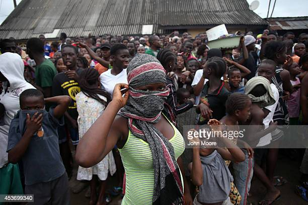 A crowd enters the grounds of an Ebola isolation center in the West Point slum on August 16 2014 in Monrovia Liberia A mob of several hundred people...