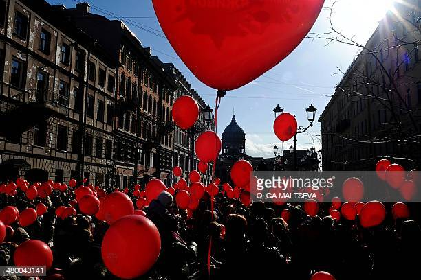 A crowd gather in the centre of St Petersburg holding red balloons during the 'Heart of the City' flashmob on March 22 2014 AFP PHOTO / OLGA MALTSEVA
