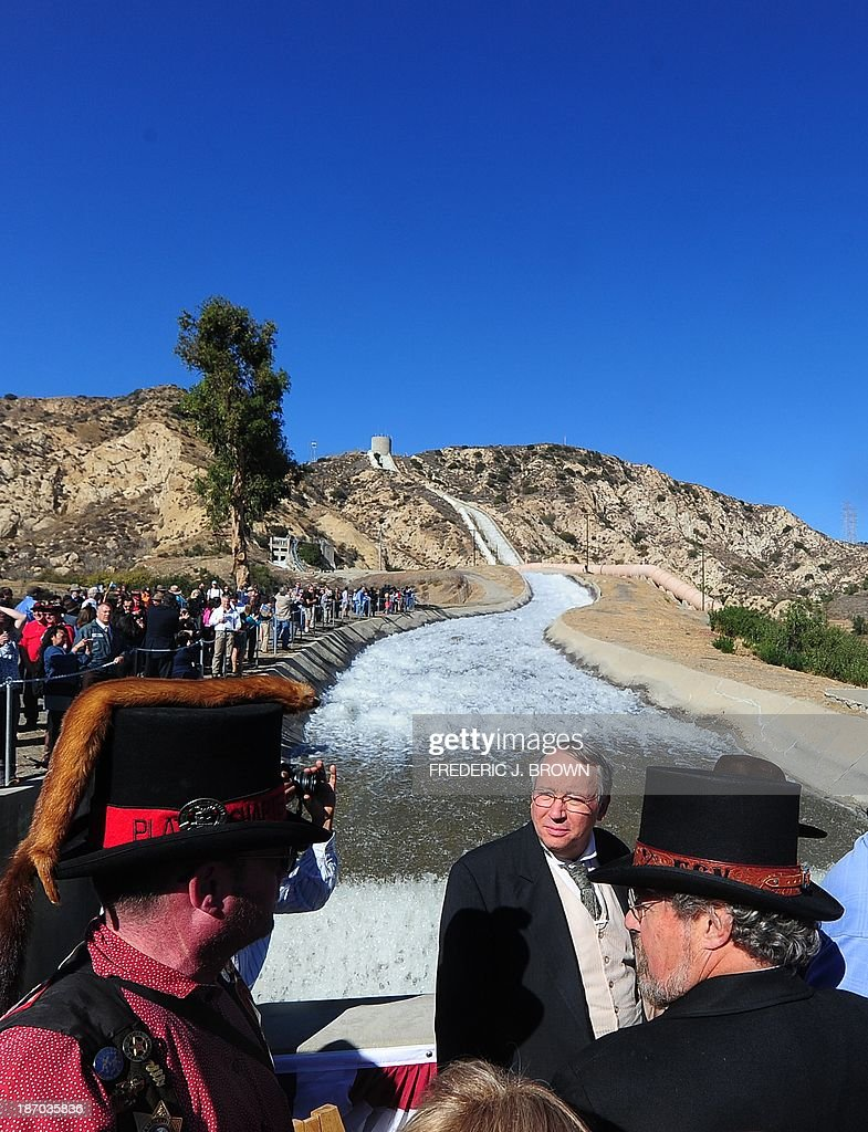 A crowd gathered, some dressed in the fashions of the past, to watch a re-enactment of the moment the Los Angeles Aqueduct gates were first opened 100 years ago, on November 5, 2013 in Sylmar, California, sending water gushing towards the city during an event marking the 100th anniversary of the opening of the 233-mile Los Angeles Aqueduct, which transports water from the Owens Valley to Los Angeles. The aqueduct started bringing water from the Owens River on the eastern slope of the Sierra Mountains to Los Angeles in November 1913 and the massive public works project is widely credited with transforming Los Angeles from a sleepy agricultural town into a modern metropolis, allowing for the city's rapid expansion. AFP PHOTO/Frederic J. BROWN