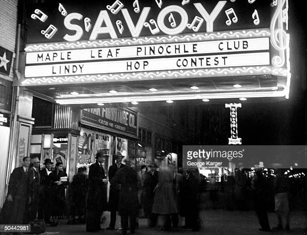 Crowd gathered under Savoy Ballroom marquis announcing a lindy hop contest at night
