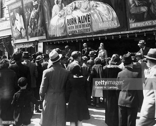 A crowd gathers around an announcer at a sideshow on the boardwalk at Coney Island Brooklyn New York City 1930s