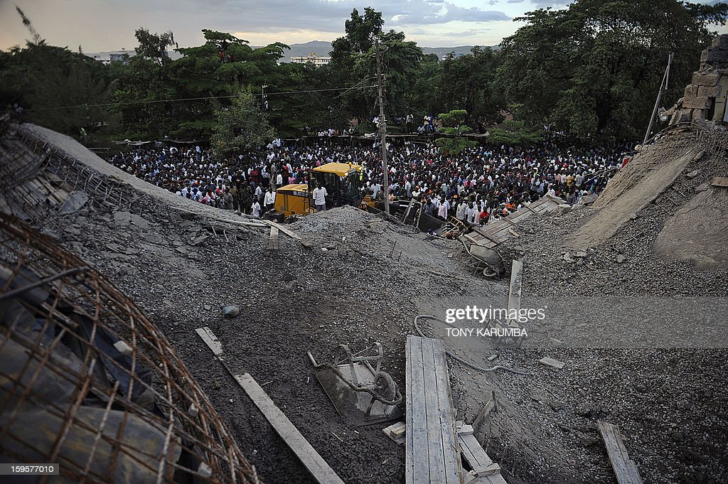 A crowd gathers at the scene of a building collapse on January 16, 2013 at Kenya's lakeside town of Kisumu killing at least three people. The building that was still under construction is suspected to have caved in due to the failure of the site's contractors to adhere to appropriate standards of construction. AFP PHOTO/Tony KARUMBA
