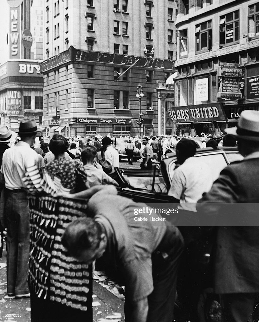 A crowd gathers at the southern end of Times Square to read the news ticker on the New York Times building as it announces victory over Japan in World War Two, 42d Street and Broadway, Manhattan, New York, August 14, 1945.