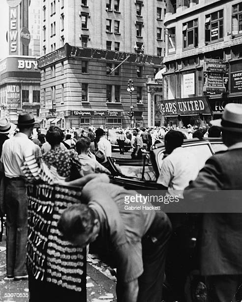 A crowd gathers at the southern end of Times Square to read the news ticker on the New York Times building as it announces victory over Japan in...