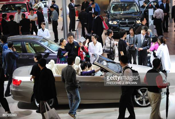 A crowd gathers on the showroom floor as a couple test feel a BMW 330i convertible on display at the Beijing Auto Show on April 21 2008 The world's...