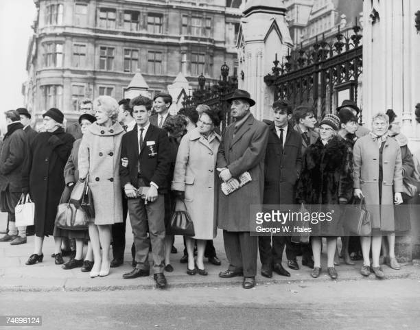 A crowd gathers outside the Houses of Parliament in London to watch politicians arrive for James Callaghan's first budget announcement as Chancellor...