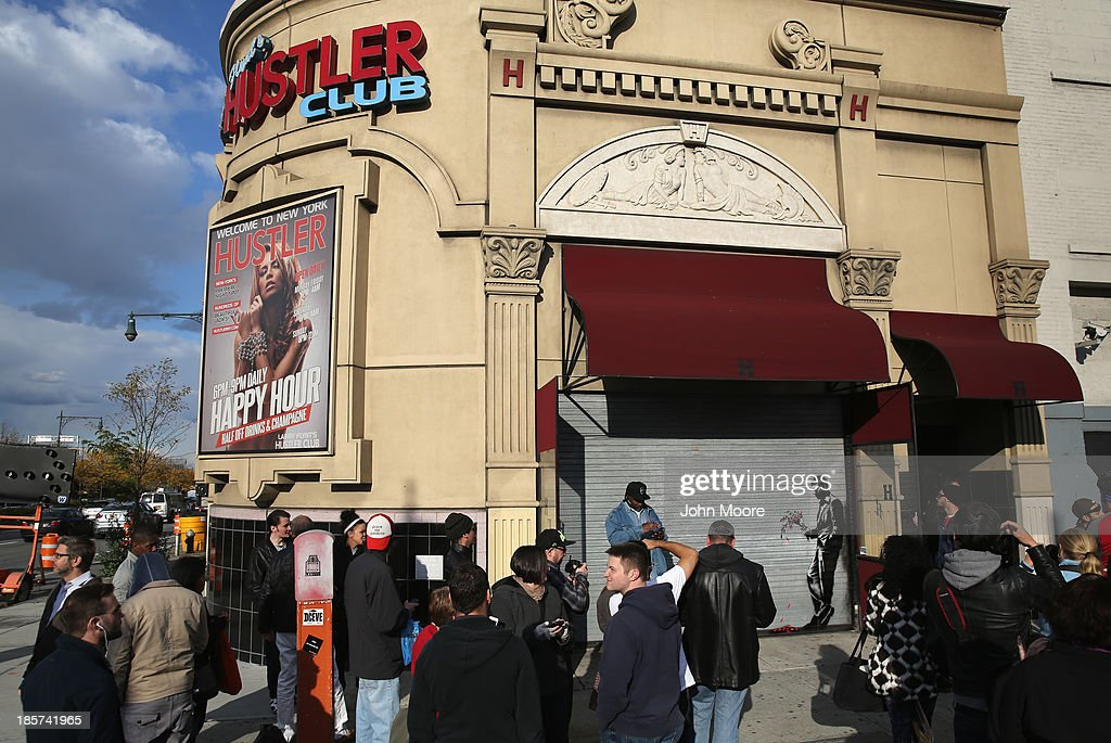 A crowd gathers to see a painting by British street artist Banksy on a roll-down security gate covering the main entrance to Larry Flint's Hustler Club on October 24, 2013 in the Hell's Kitchen neighborhood of New York City. On Banksy's website a caption for the work reads, 'Waiting in vain...at the door of the club.'