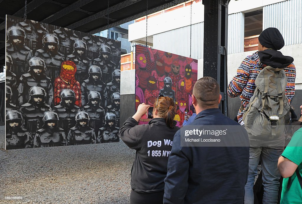 A crowd gathers to view Banksy's latest work October 18, 2013 in the Chelsea neighborhood of New York City. The British street artist Banksy has been creating new street art for the month of October in New York.
