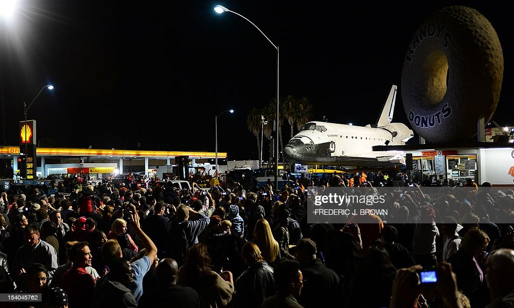 A crowd gathers to view the US space shuttle Endeavour at Randy's Donuts before it crosses Manchester Bridge above the 405 Freeway at La Cienega on its final journey through city streets in Los Angeles to a permanent home at the California Sciene Center, on October 12, 2012 in California. The shuttle which flew more than 115 million miles (185 million kilometers) in its two-decade career, has begun its final journey at the less-than rocket-propelled speed of 2 mph (3.2 kmh), in a meticulously planned trip through the streets of Los Angeles. The shuttle is mounted on a high-tech flatbed carrier for the trip, which at certain points will involve squeezing round corners within inches of buildings. AFPHOTO / Frederic J. BROWN