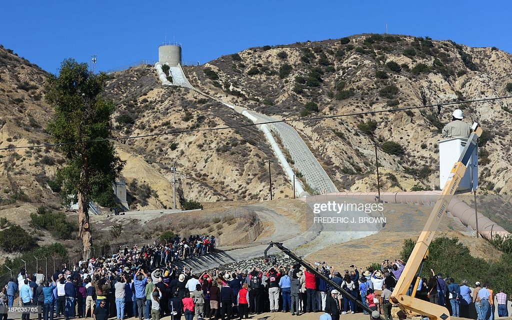 A crowd gathers to watch a re-enactment of the moment the Los Angeles Aqueduct gates were first opened 100 years ago, on November 5, 2013 in Sylmar, California, sending water gushing towards the city during an event marking the 100th anniversary of the opening of the 233-mile Los Angeles Aqueduct, which transports water from the Owens Valley to Los Angeles. The aqueduct started bringing water from the Owens River on the eastern slope of the Sierra Mountains to Los Angeles in November 1913 and the massive public works project is widely credited with transforming Los Angeles from a sleepy agricultural town into a modern metropolis, allowing for the city's rapid expansion. AFP PHOTO/Frederic J. BROWN