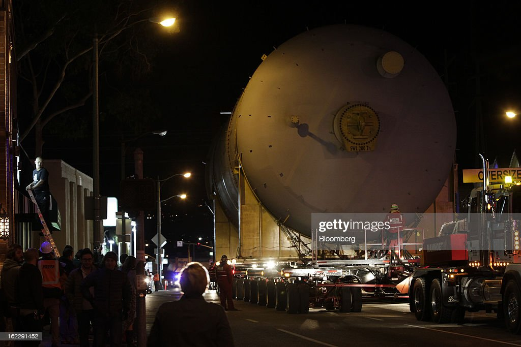 A crowd gathers to watch a steel coke drum on a trailer manufactured by Mammoet Salvage BV as it travels along the Pacific Coast Highway between Redondo Beach and El Segundo, California, U.S., on Wednesday, Feb. 20, 2013. The drum, which measures over 100 feet long and weigh 500,000 pounds is one of six scheduled to be delivered to Chevron Corp.'s refinery in El Segundo. Photographer: Patrick Fallon/Bloomberg via Getty Images