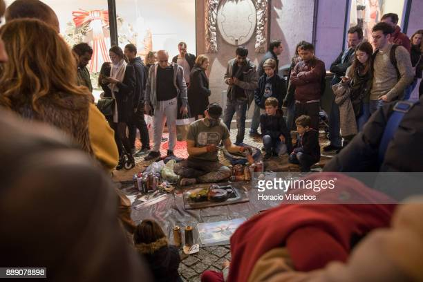 A crowd gathers under Christmas and New Year light displays in Rua do Carmo to watch the work of a street painter on December 9 2017 in Lisbon...