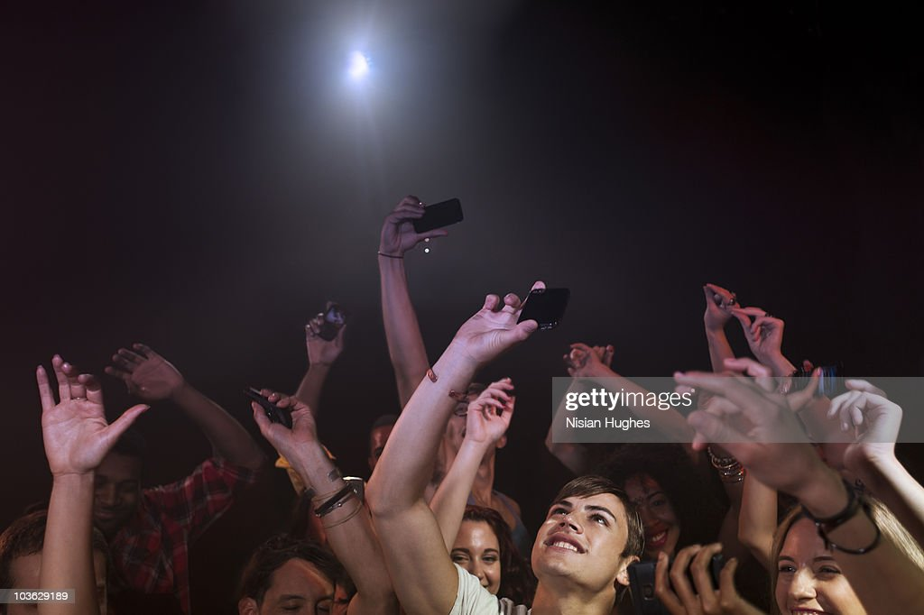 crowd in nightclub holding up cell phones : Stock Photo