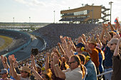 Crowd in stadium watching stock car racing, cheering, side view