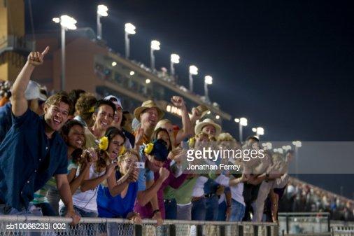 Crowd in stadium watching stock car racing, leaning on railings, cheering