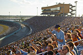 Crowd in stadium watching stock car racing, man standing out from crowd, side view