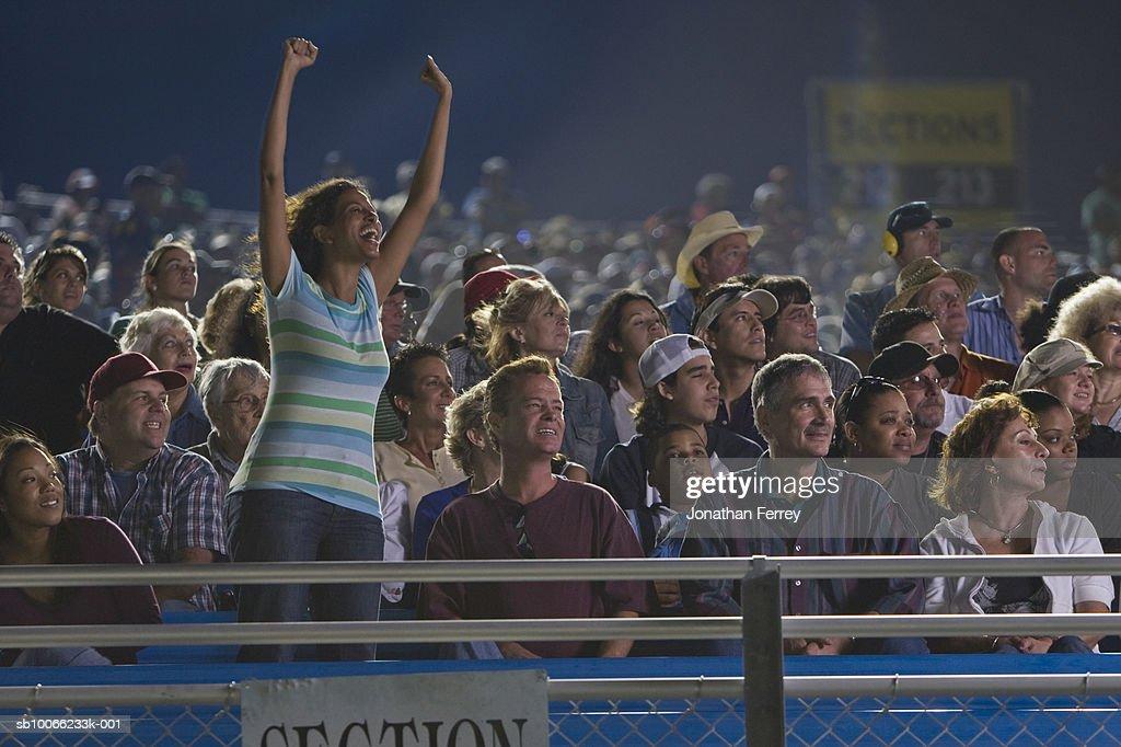 Crowd in stadium watching stock car racing, woman cheering