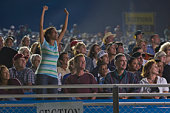 Crowd in stadium watching stock car racing, woman cheering