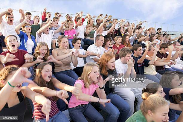 A crowd in the stands boos and points to the field at an outdoor event