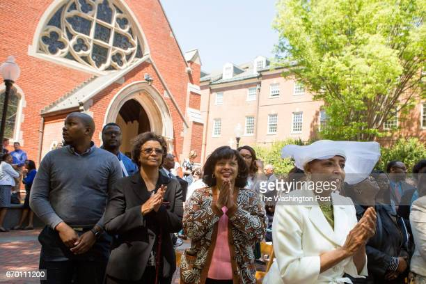 A crowd including Onita EstesHicks in hat cheers at the conclusion of a dedication of Isaac Hawkins and Anne Marie Becraft halls at Georgetown...