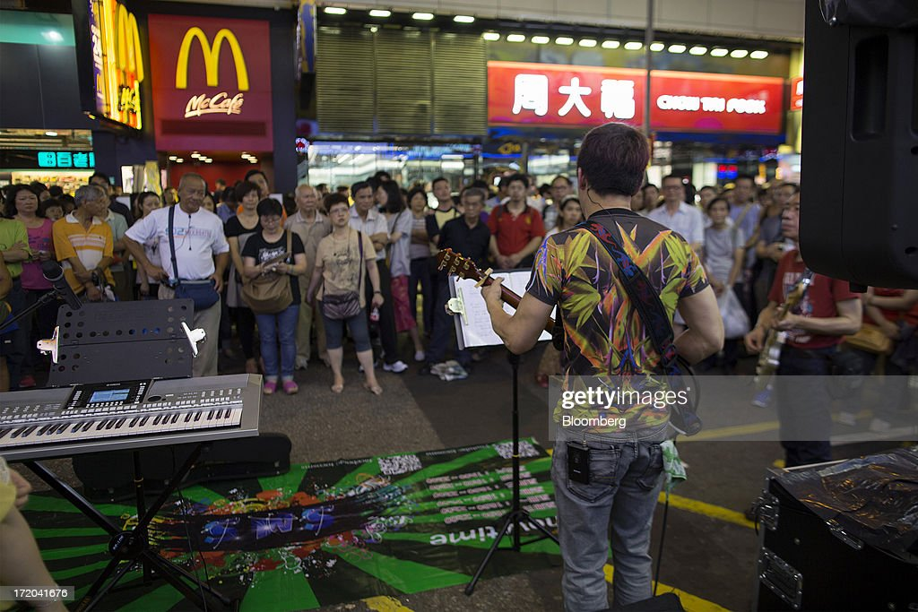 A crowd listens to a busker in the Mong Kok district of Hong Kong, China, on Saturday, June 29, 2013. Hong Kongs best-selling newspapers called on readers to join a march to mark the anniversary of the citys handover to China, saying the government has failed to address issues of poverty and universal suffrage. Photographer: Jerome Favre/Bloomberg via Getty Images