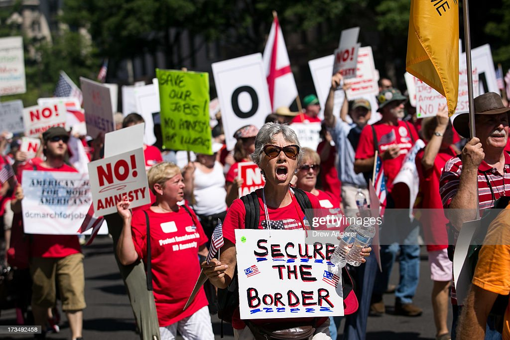 A crowd marches along Pennsylvania Avenue during the DC March for Jobs on July 15, 2013 in Washington, DC. Conservative activists and supporters rallied against the Senate's immigration legislation and the impact illegal immigration has on reduced wages and employment opportunities for some Americans.