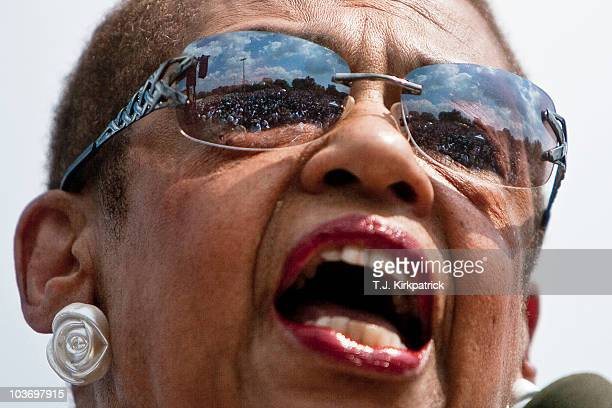 A crowd numbering in the thousands is reflected in the sunglasses of Delegate Eleanor Holmes Norton while she speaks at a rally at Dunbar High School...